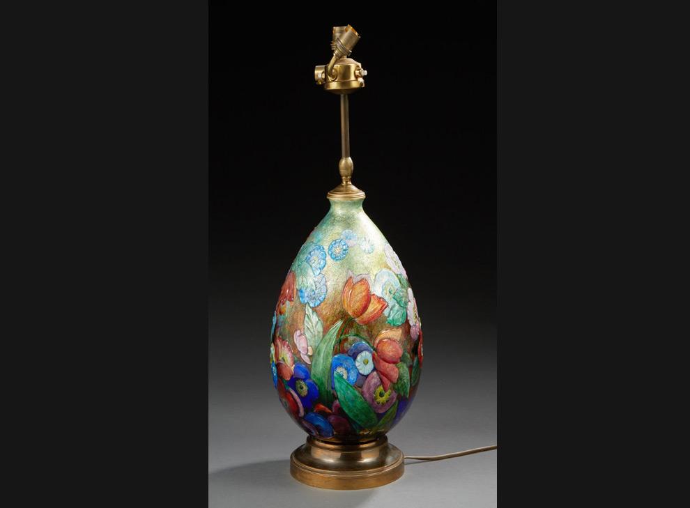 Grande lampe de forme ovoïde en cuivre émaillé de motifs floraux en polychromie. Elle repose sur une base circulaire en laiton doré.