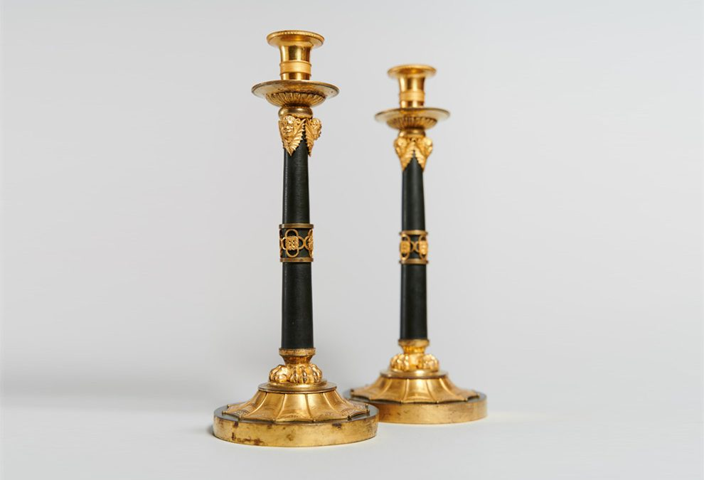 A pair of ormolu and patinated bronze candlesticks